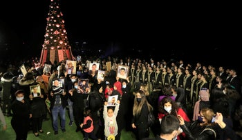 Relatives of victims killed during the Beirut port explosion hold up their portraits as they stand next to a Christmas tree decorated with names of those who died, Beirut, Lebanon, December 21, 2020.