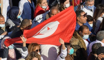 Tunisian protesters wave their country's national flag during a demonstration in the capital Tunis, December 8, 2020.