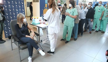 Doctors as Ichilov hospital in Israel watching a woman get COVID-19 vaccine, December 22, 2020.