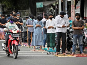 A motorist passes Muslims performing Friday prayer wearing masks to help curb the spread of the coronavirus outside a crowded mosque in Jakarta, Indonesia, October 2, 2020.