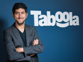 Taboola CEO Adam Singolda posing in front of his company's logo, August 11, 2015