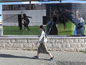 A young woman walks past the defaced pictures in Jerusalem, December 2020.