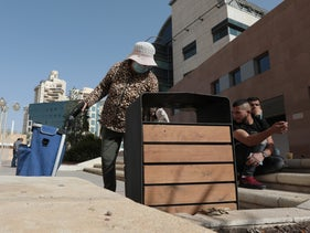 A woman looking through a garbage bin in Be'er Sheva, November 2020.