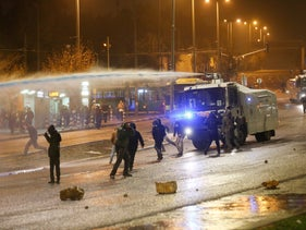 Police use water cannon at protest in front of national police headquarters.