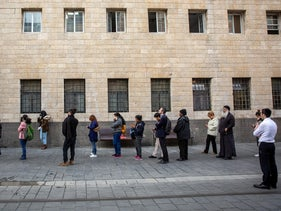 Jerusalemites wait in line to enter a post office, March 2020.