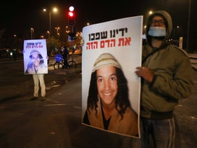 A protester in Jerusalem holding a sign showing Israeli teen Ahuvia Sandak, who was killed in a police car chase in the West Bank, December 27, 2020.