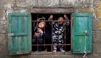 Palestinian children look out of their family's home window on a rainy day at Deir al-Balah refugee camp in the central Gaza Strip December 17, 2020.