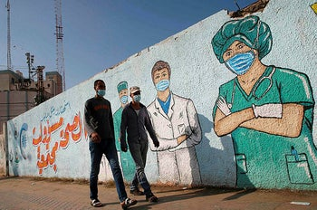 Palestinian men walk past street art showing doctors mask-clad due to the pandemic, in Khan Yunis in the southern Gaza Strip.