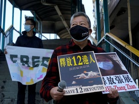 Pro-democracy activists hold placards with the picture of the Chinese citizen journalist Zhang Zhan as they march to the Chinese central government's liaison office, in Hong Kong, December 28, 2020.