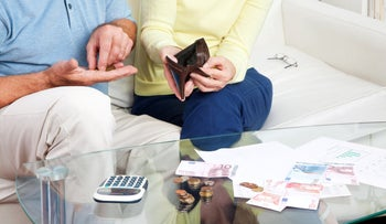 Illustration: An elderly couple counts money on the living room table.