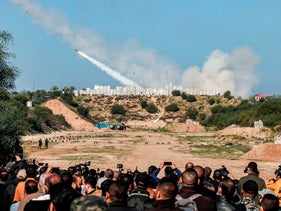 People watch as rockets are fired during a military drill by Palestinian Islamist movement Hamas and other Palestinian armed factions near Gaza City on December 29, 2020.