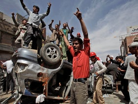 Yemeni anti-government demonstrators shout at supporters of President Ali Abdullah Saleh in Sanaa, Yemen, Feb. 22, 2011.