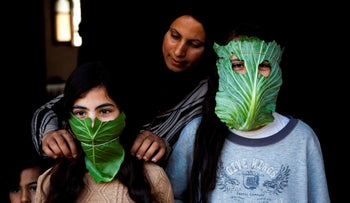 A Palestinian mother entertain her children with makeshift masks made of cabbage as she cooks in Beit Lahia in the northern Gaza Strip on April 16, 2020.