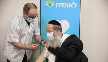 Mayor Rabbi Avraham Rubinstein of Bnei Brak receives the first dose of the coronavirus vaccine at the central Leumit health maintenance organization clinic, Tel Aviv, December 20, 2020.