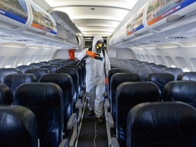 An Israeli worker in full hazmat suit sprays disinfectant in the cabin of an Israir airplane, at the Ben Gurion International Airport, June 14, 2020.