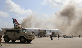 A military vehicle is seen on the tarmac as dust rises after explosions hit Aden airport, upon the arrival of the newly-formed Yemeni government in Aden, Yemen December 30, 2020.