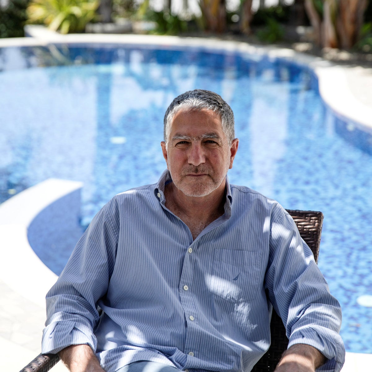 Tal Dilian sits next to his pool in his Limassol home. He was photographed by Reuters as part of a story about using spytech to help track the spread of the coronavirus