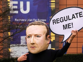 """- A campaigner from the global citizens movement Avaaz wearing a mask of Facebook CEO Mark Zuckerberg holds a sign reading """"Regulate me"""""""