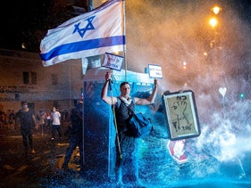 An anti-Netanyahu demonstrator holds the Israeli flag as he is being shot by a water cannon during a demonstration outside the prime minister residence in Jerusalem, in July.