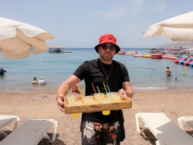 A beachgoer carrying drinks in plastic glasses at a beach in Eilat, 2019.