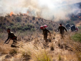 Soldiers, near Kibbutz Be'eri, working to extinguish fires set off by incendiary balloons sent from Gaza last summer.