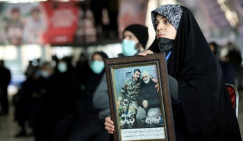 An Iranian woman holds a picture of Qassem Soleimani during a ceremony marking the anniversary of his killing, in Tehran, Iran January 1, 2021.