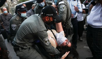 Police officers carry away a protester in anti-Netanyahu protests in Jerusalem, January 2, 2021.