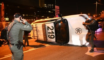 A police car flipped over by protesters during a demonstration over settler teen's death in police chase, Jerusalem, January 2, 2021.