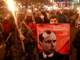 Activists and supporters of Ukrainian nationalist parties hold torches as they take part in a rally to mark the 112th birth anniversary of Stepan Bandera, in Kyiv, Ukraine, January 1, 2021.
