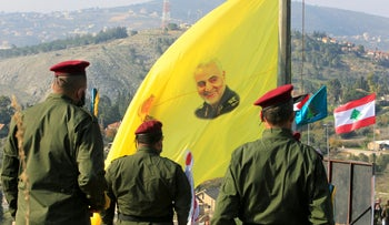 Members of Hezbollah stand near a flag with a picture of Qassem Soleimani, during a ceremony marking the first anniversary of his killing in the southern Lebanese village of Khiam, January 3, 2021.