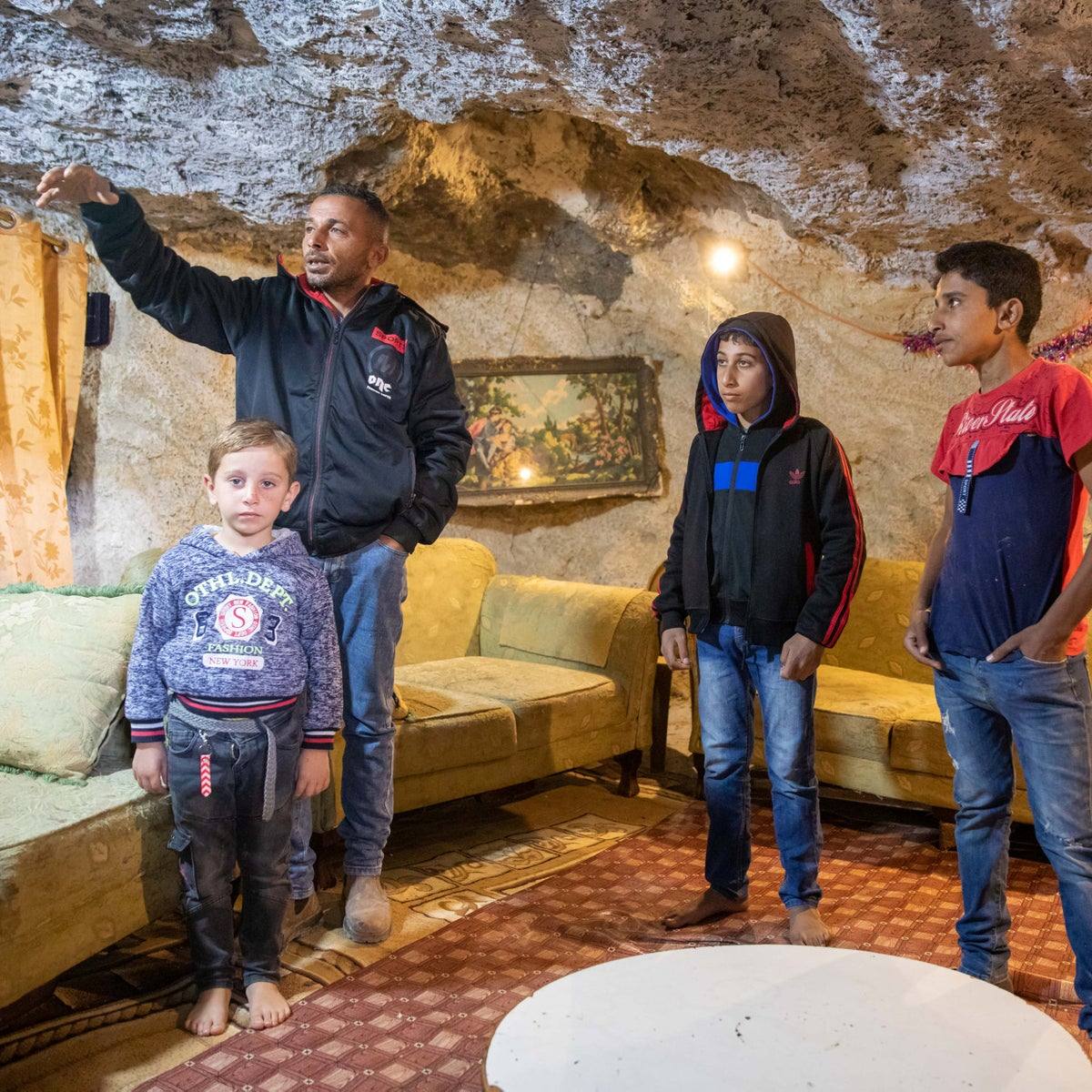 Ashraf Amour and family members inside their home, in a cave in the village of Khirbet al-Rakiz, in the West Bank's south Hebron Hills.