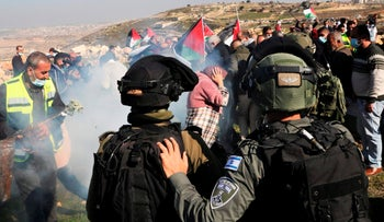 Israeli forces use tear gas to block Palestinians trying to reach their confiscated lands, during a protest in the village of Halhul, north of Hebron, January 4, 2021.