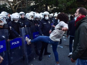 Police in riot gear clash with students of Bogazici University, in Istanbul, Monday, Jan. 4, 2021. Turkish police on Monday clashed with hundreds of students protesting President Recep Tayyip Erdogan's appointment of a figure with ties to his ruling party as rector to one of Turkey's most prestigious universities