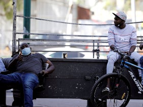 Sudanese migrants sit as they wait for work on a street corner in south Tel Aviv, October, 25, 2020.