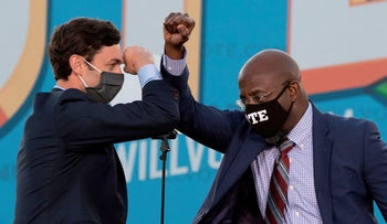 Democratic candidates for Senate Jon Ossoff and Raphael Warnock bump elbows on stage during a rally with US President-elect Joe Biden in Atlanta, Georgia. Jan 4, 2021