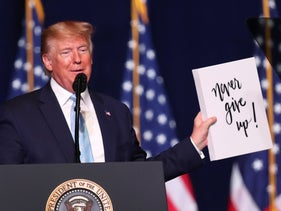 "President Donald Trump holding up a sign reading 'Never give up!' given to him during a ""Evangelicals for Trump"" campaign event in Miami, Florida, January 2020."
