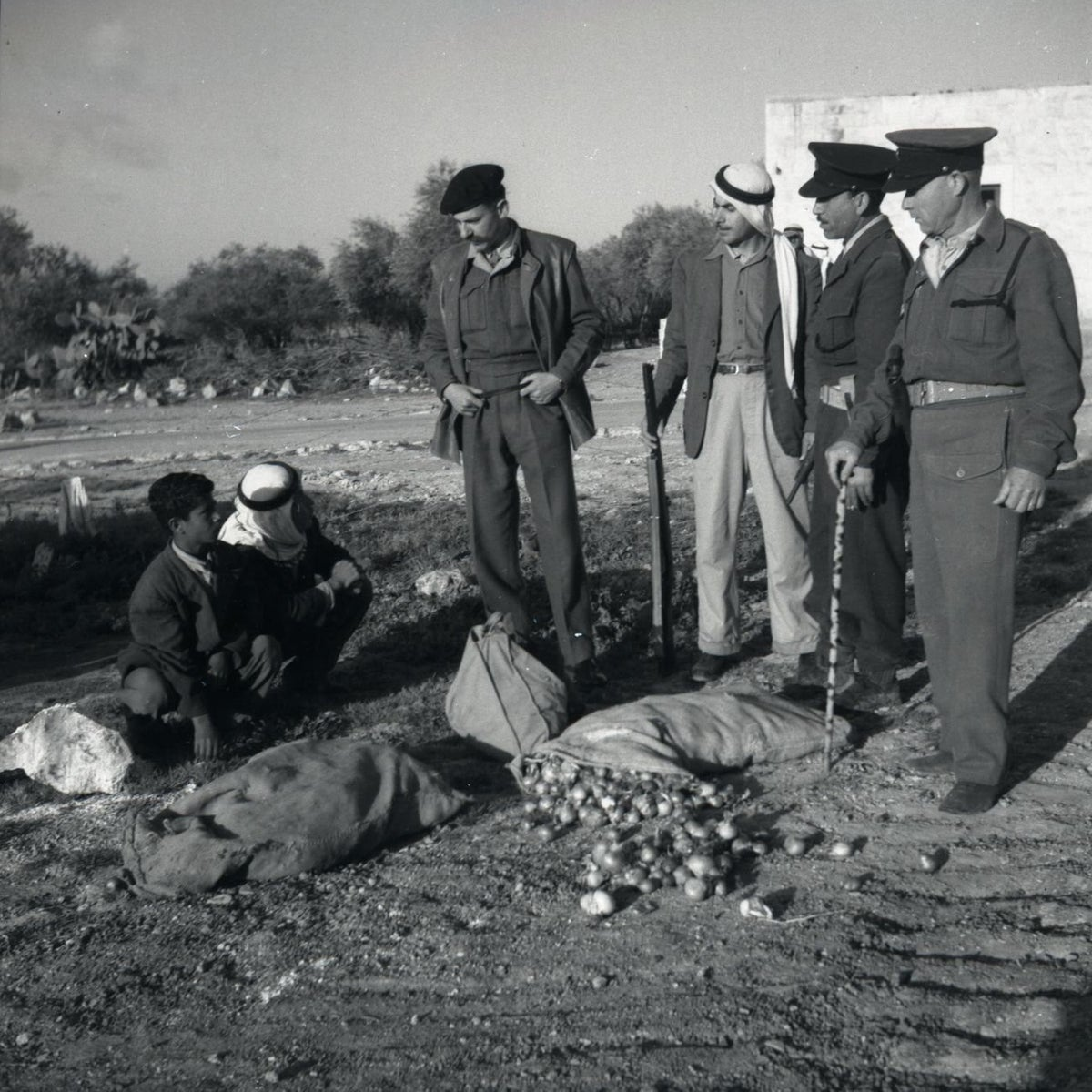 Military policemen inspect a suspicious sack of onions found in possession of Arab citizens, in 1952.