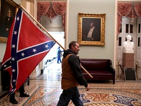 A supporter of President Donald Trump carries a Confederate battle flag on the second floor of the U.S. Capitol in Washington, U.S., January 6, 2021.