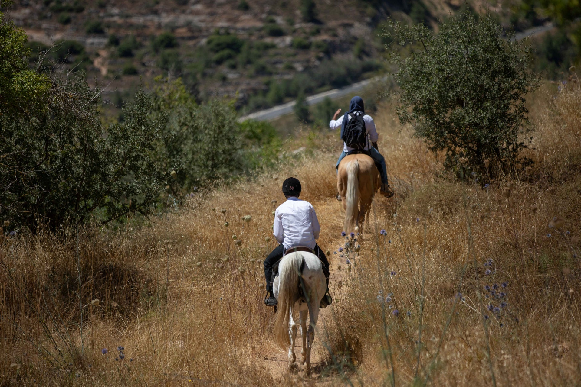 People ride on horseback in the Reches Lavan are, west of Jerusalem, June 2020. A mass construction project will build thousands of units, severely impacting the landscape.