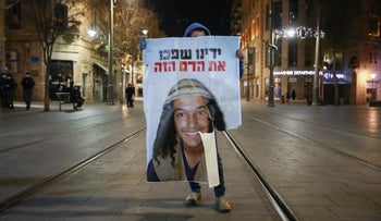 A protester holds a poster with a picture of Ahuvia Sandak in Jerusalem, December 30, 2020. The subject has no connection to the content of the article.