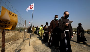 Pilgrims march towards the Jordan River to participate in a baptism ceremony at the Qasr el-Yahud site, near Jericho, West Bank, January 10, 2021.