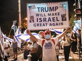 A Likud supporter holding a sign reading reading 'Trump will make Israel great again.'