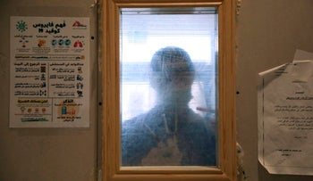 A Palestinian health professional is pictured behind a window at the Dura public hospital in Hebron, December 18, 2020.