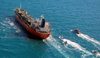 A seized South Korean-flagged tanker is escorted by Iranian Revolutionary Guard boats on the Persian Gulf on Jan. 4, 2021.
