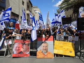 Supporters of Benjamin Netanyahu hold posters with Avichai Mendelblit's photo during the opening session of Netanyahu's trial in Jerusalem, May 24, 2020.