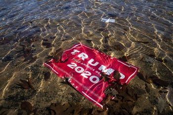 A campaign sign for U.S. President Donald Trump lies underwater in the Capitol Reflecting Pool. January 9, 2021
