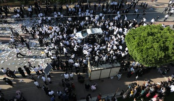 Ultra-Orthodox protesters surround a police car in Ashdod, January 11, 2020.