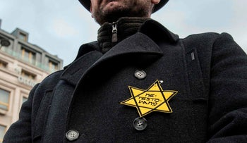A man with a Nazi like star of David reading 'untested' takes part in a protest in Prague, January 8, 2021.