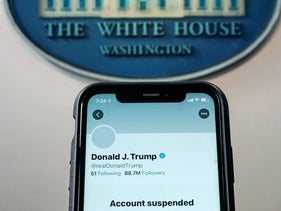 the suspended Twitter account of U.S. President Donald Trump on a smartphone at the White House briefing room in Washington, U.S., January 8, 2021