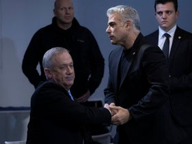 Benny Gantz (sitting) shakes Yair Lapid's hand during a campaign event in Tel Aviv, December 12, 2019.